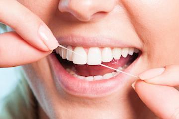 woman flossing to keep gums healthy