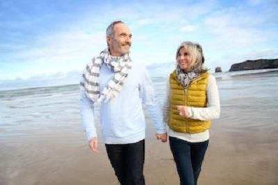 Older couple holding hands while walking on beach