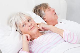 woman plugging ears while husband snores beside her