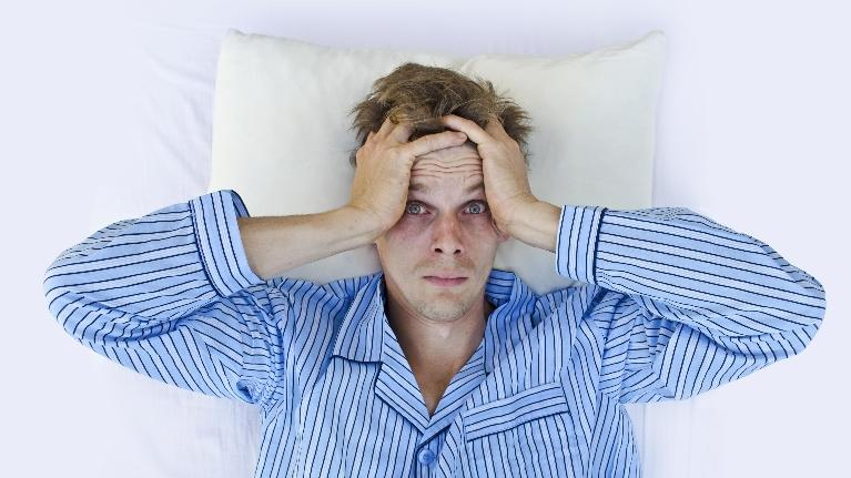 a man lays awake in bed | sleep apnea treatment manhattan beach ca