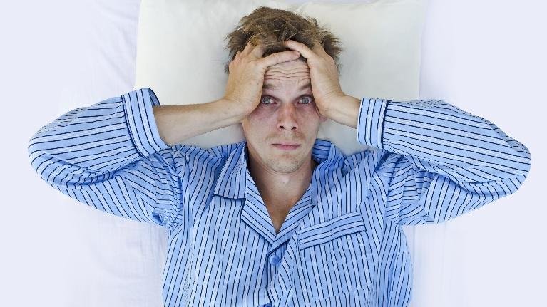 A man lies awake in bed with his hands on his head | Manhattan Beach CA sleep apnea treatment